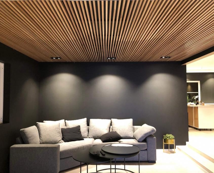 Sofagruppe med downlights i tak mot mørk bakvegg