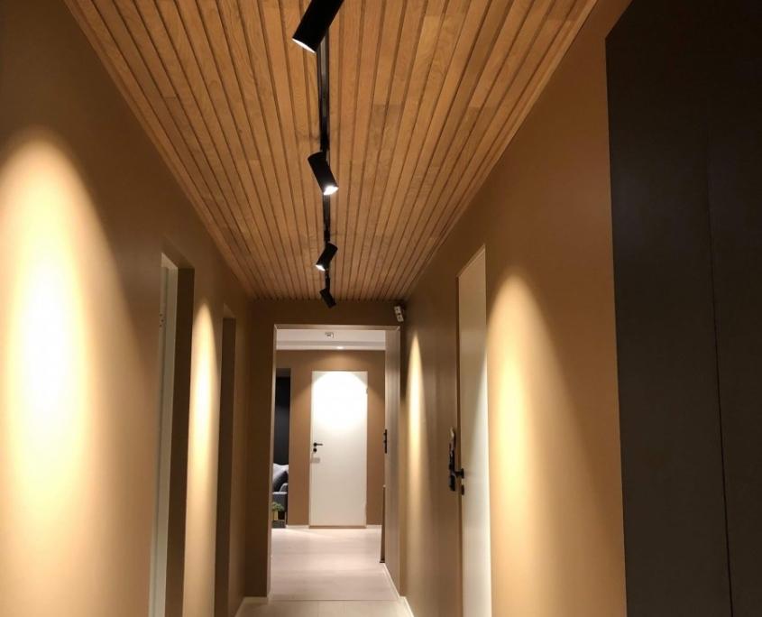 Innendørs gang i trevirke og led-spotlights i taket